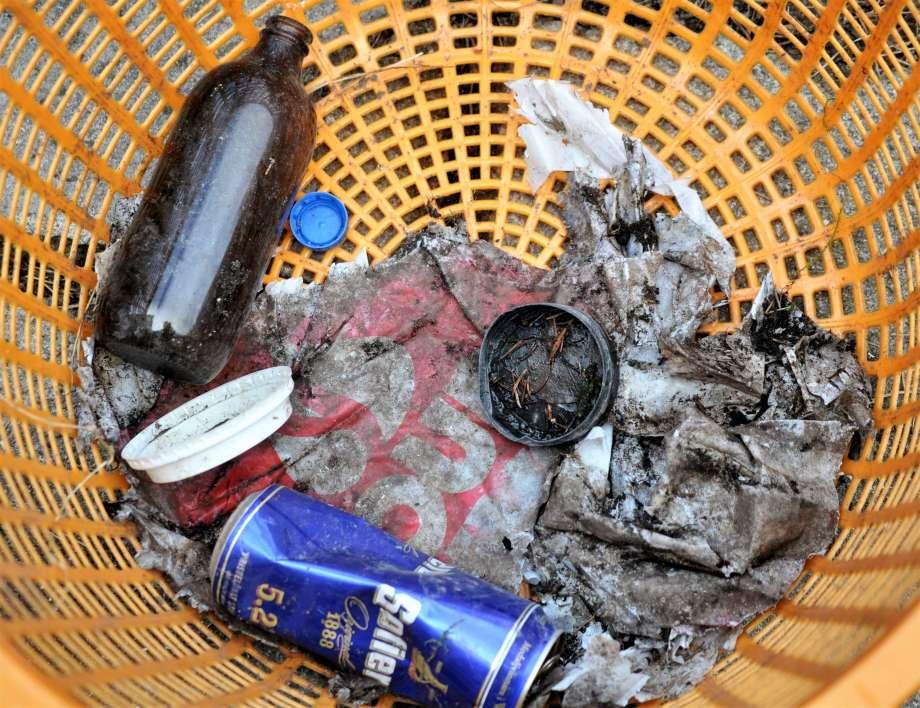 skräp ihopsamlat från vägrenen ölburk snusdosa flaska och plastkasse