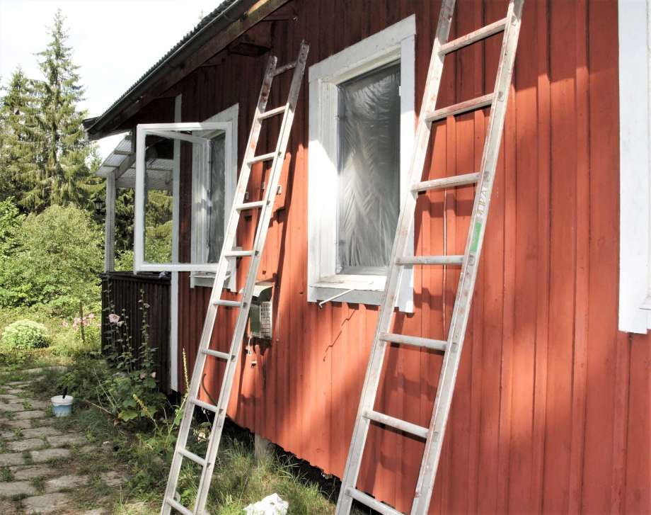 två stegar lutade mot väggen till en rödvit stuga. Ett fönster uppställt och ett annat ersatt av plast.