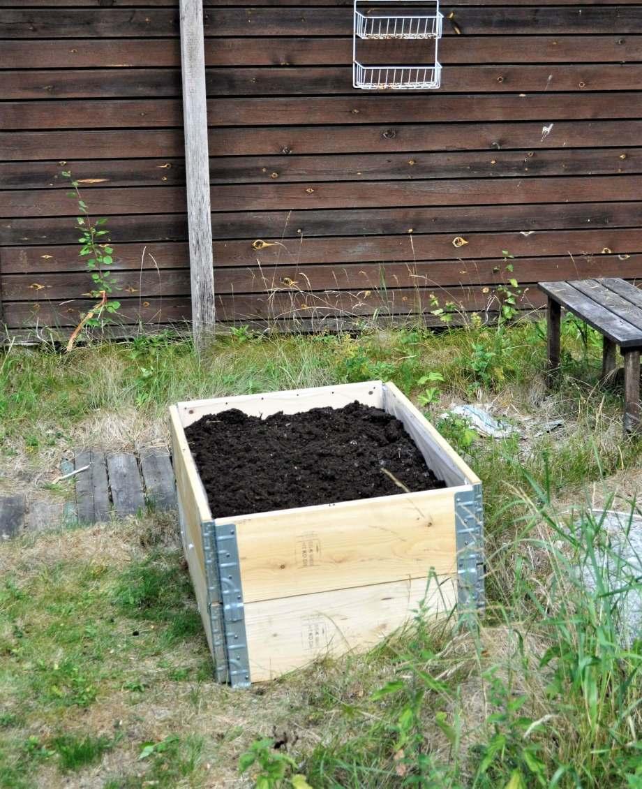 liten pallkrage utan växter framför husvägg