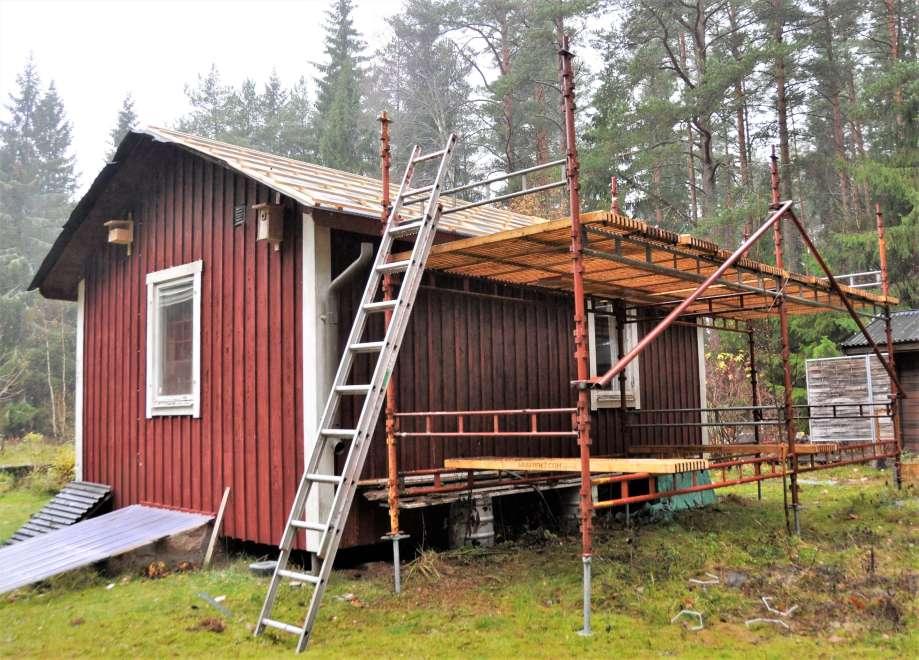 byggnadsställning och stege uppställda på baksidan av gäststugan