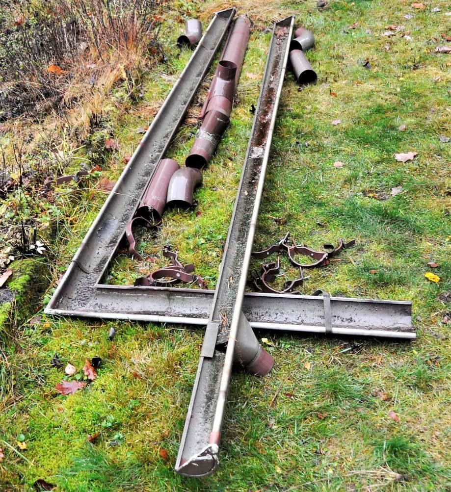 bitar av nedmonterade stuprör och hängrännor utlagda på gräsmattan