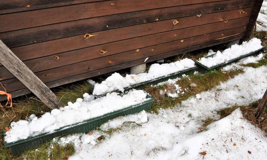 tre blomlådor stående på marken, nu täckta med snö