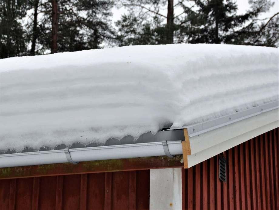många lager av snö på taket blir sammanlagt en tjock snölasagne