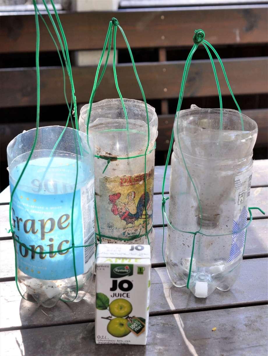 tre getingfällor av gamla Pet-flaskor står på ett verandabord tillsammans med en tetraförpackning äppeljuice