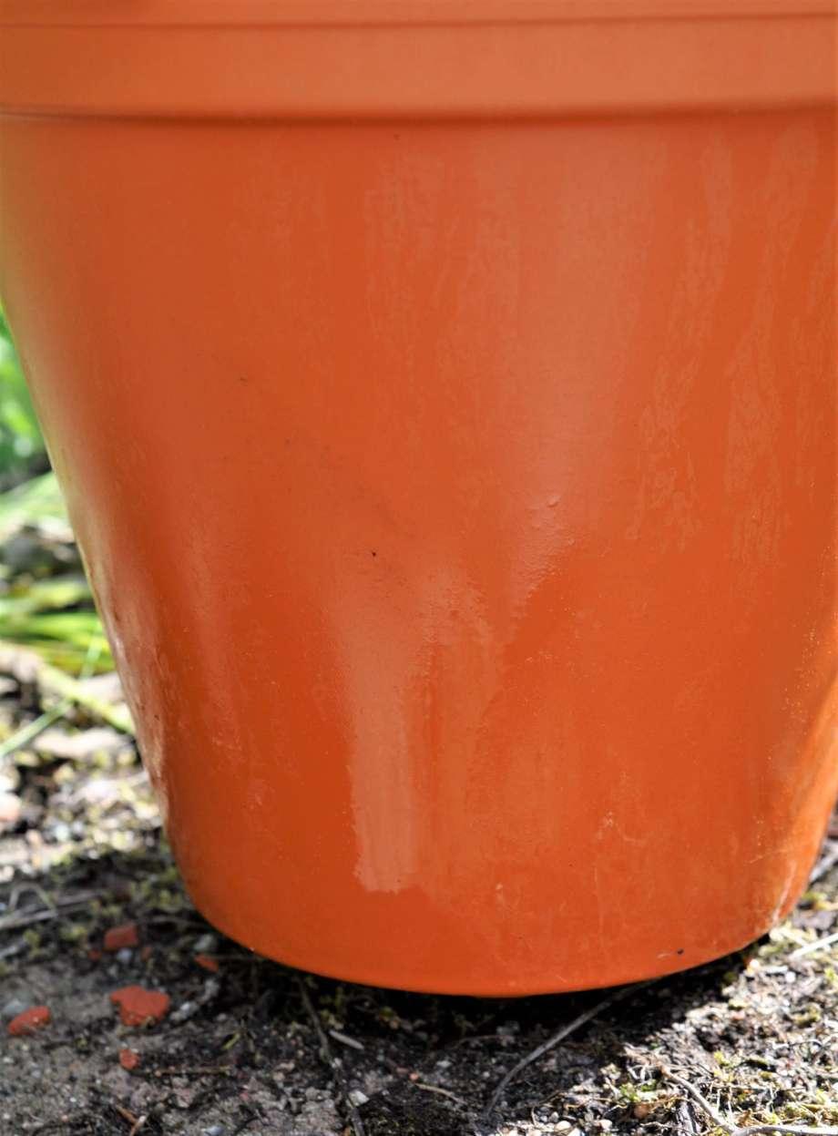 vattenkondens på utsidan av en terrakottakruka som står på grusigt underlag