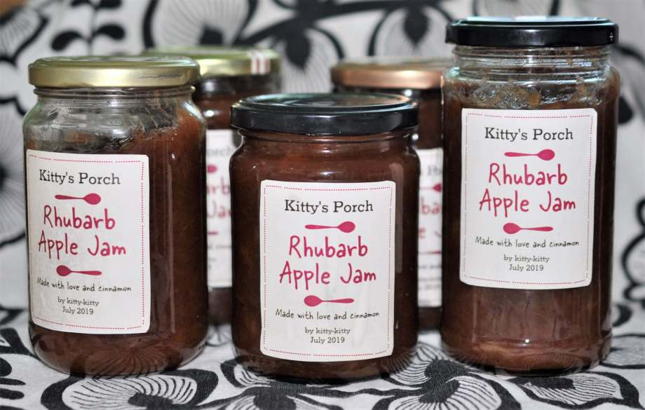 "Fem glasburkar med sylt och etiketter som säger ""Kitty's porch Rhubarb Apple Jam Made with love and cinnamon"" står på ett vitt tyg med svart bladmönster."