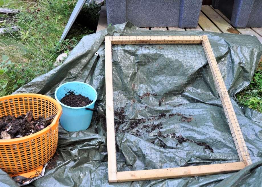 en träram med nät fastsatt lutas över grön presenning. bredvid står en blå hink och en orange lövkorg fyllda med jord.
