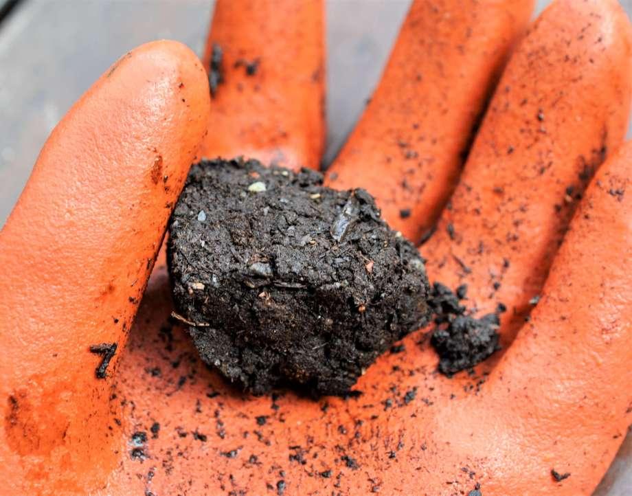 en ihoppressad jordklump ligger i handflatan på en orange gummihandske.