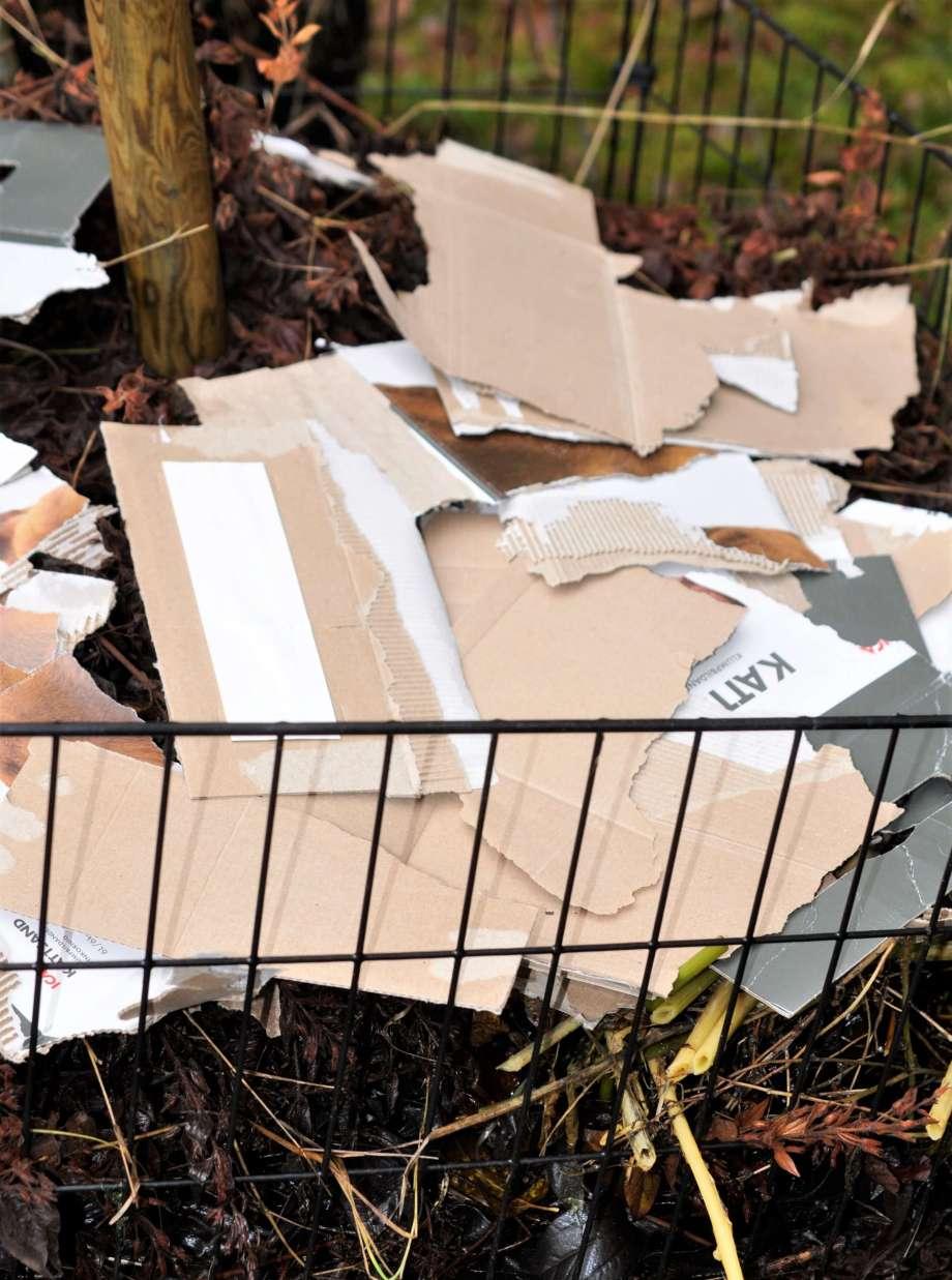 kartongbitar utlagda överst i grönkomposten
