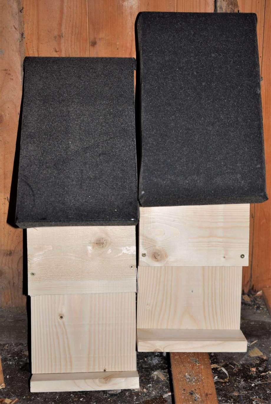 två nysnickrade fladdermusholkar står lutade mot väggen till vedboden