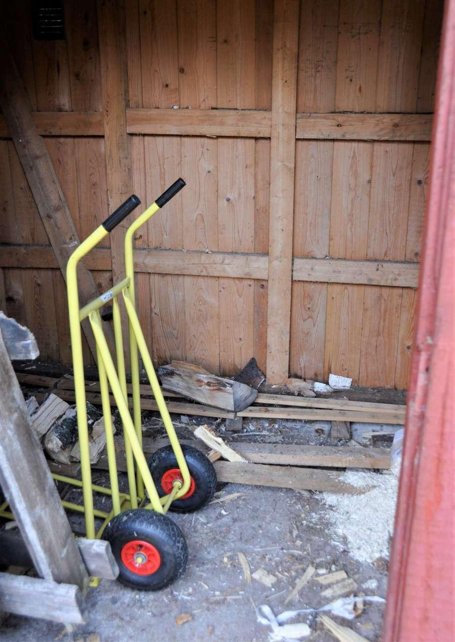 tom vedbod med en gul pirra och ett par enstaka vedträn på golvet