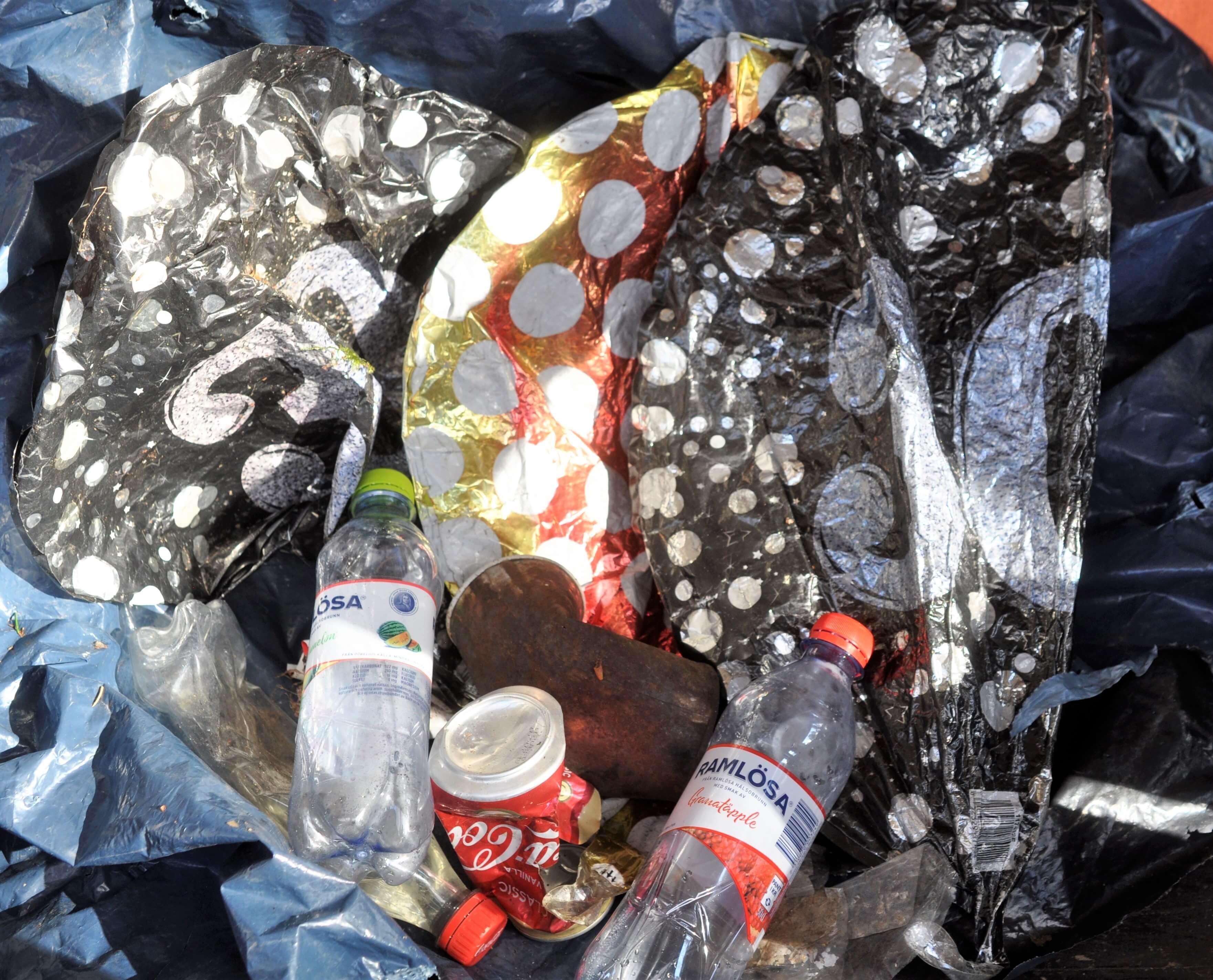 massor av plastskräp (pet-flaskor, sopsäck och tre solblekta ballonger) tillsammans med två drickaburkar