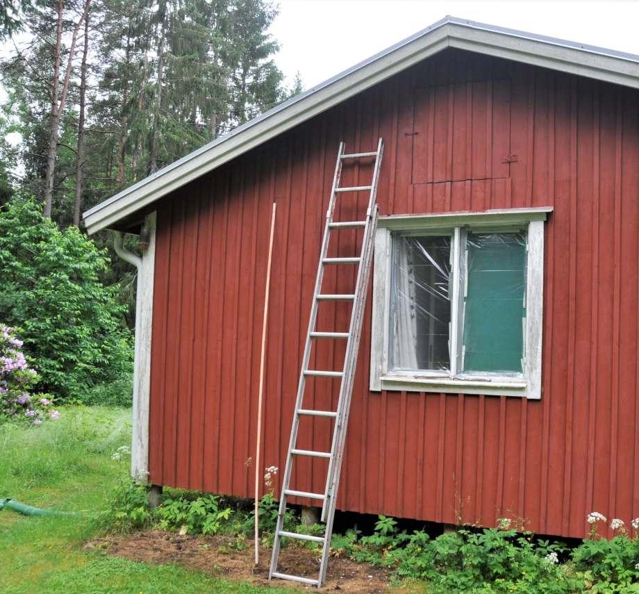 gavelsidan av ett lågt, falurött trähus med vita knutar. En stege är lutad mot väggen. Två fönsterramar saknar fönster istället är de försatta med genomskinlig plast.